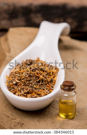 Calendula Marigold flowers in white spoon with oil on stone - stock photo