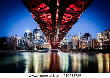CALGARY, CANADA - APRIL 27: the Peace Bridge on April 27, 2013 in Calgary, Alberta Canada. The pedestrian bridge spans the Bow River and was designed by Santiago Calatrava. Skyline in background. - stock photo