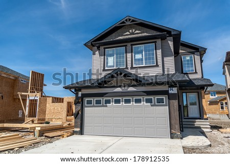 CALGARY, CANADA - AUG 11, 2007: Suburban home under construction in Royal Oak in Calgary, Alberta. This grey two-story suburban home is typical of Calgary outlying residential districts.