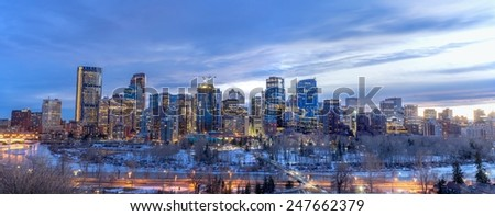 CALGARY, CANADA - JAN 24: Skyscrapers in the urban core at dusk on January 24, 2015 in Calgary, Alberta Canada.  The iconic Bow Tower is the tallest building on the skyline and is visible to the left. - stock photo