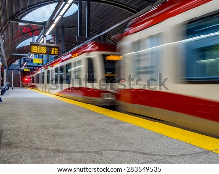 CALGARY, CANADA - MAY 24: The C-train speeding into Westbrook stations on  May 24, 2015 in Calgary, Alberta. The C-train is Calgary's light rail transit vehicle and moves over 300,000 people a day. - stock photo