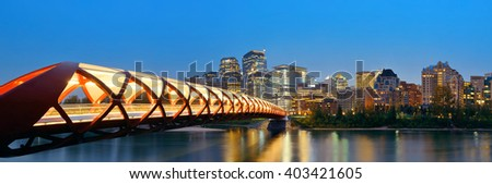 Calgary cityscape with Peace Bridge and downtown skyscrapers in Alberta at night, Canada. - stock photo