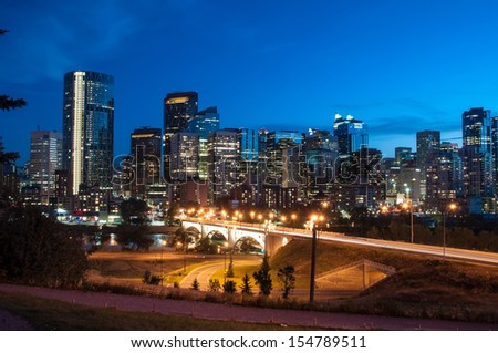 Calgary skyline at night with Bow River and Centre Street Bridge. - stock photo