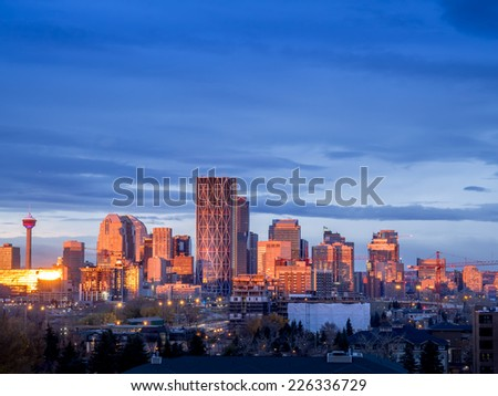Calgary skyline in the early morning with rays from rising sun reflecting off glass buildings. - stock photo