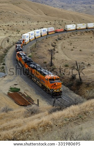 CALIENTE, CA - OCT 25, 2015: A westbound BNSF freight train, pulled by diesel-electric engines, slowly descends out of the Sierra Nevada Range. It's about to enter one of many tunnels along the route.