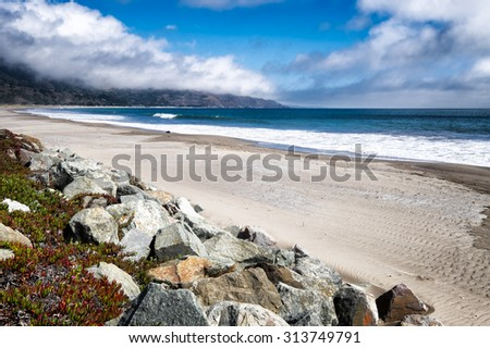 California beach. Miles of white sand. Boulders in the foreground with colorful ice plant. Location: Stinson Beach, north of San Francisco. - stock photo