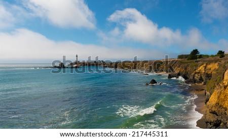California coast. Famous lighthouse on a rock. Ocean waves wash the beach. Clouds on the blue sky. - stock photo