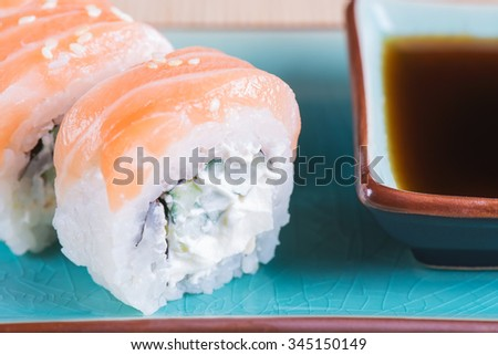 California maki sushi with fish. Roll made of salmon, cream cheese and  cucumber. Shallow depth of field.  - stock photo