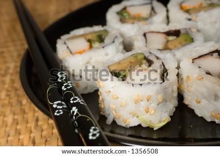 California rolls on black plate with chopsticks - stock photo