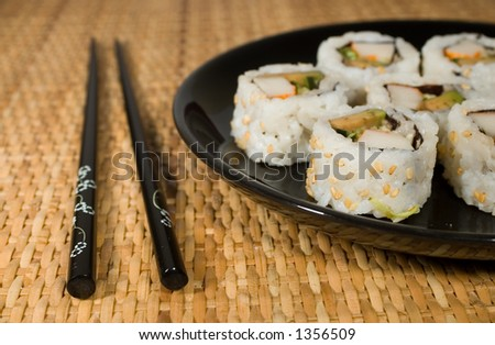 California rolls on black plate with chopsticks on placemat - stock photo