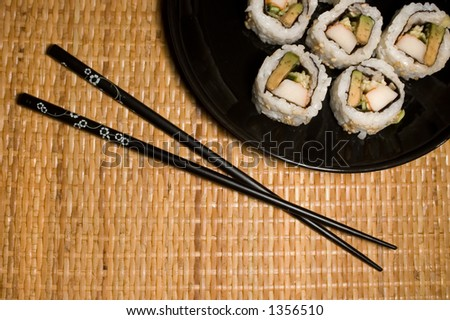 California rolls on black plate with copsticks. - stock photo