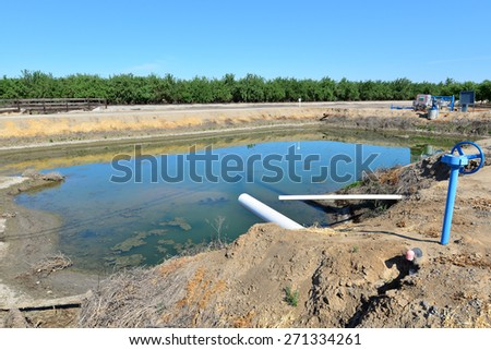 California's serious drought is reflected in the low water level in this Kern County irrigation pond. - stock photo