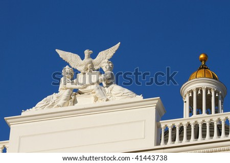 California State Capitol sculpture of two women or girls holding hands across the US shield with an eagle above with Capitol Gold Dome in back - stock photo