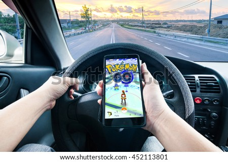 California, United State, July 2016 : Hand holding a cellphone playing Pokemon Go game while driving indicating dangerous - stock photo