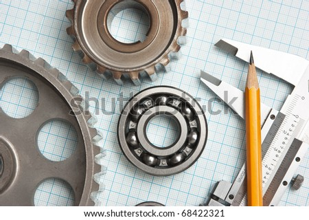 caliper with gears and bearings on graph paper