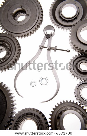 Calipers, nuts and cogwheels over white - stock photo