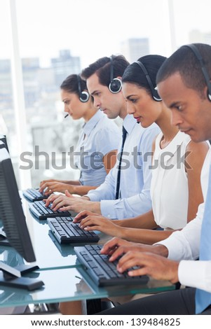 Call center employees sitting in line in a workplace - stock photo