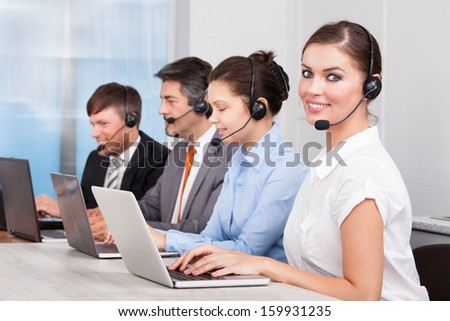 Call center operator sitting in row working at office - stock photo