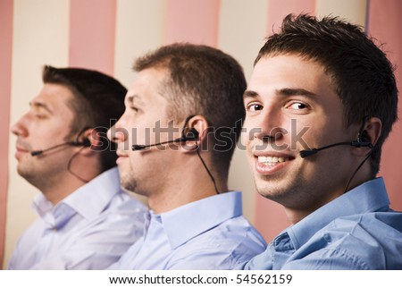 Call center operators with three men team at work in office,first man facing camera and smiling
