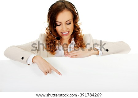 Call center woman pointing on empty banner. - stock photo