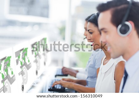 Call center workers at work on futuristic interfaces showing maps in bright modern office - stock photo