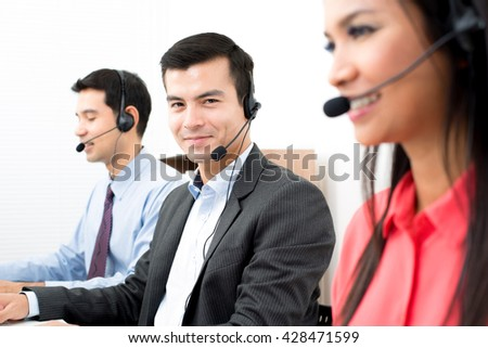 Call center workers wearing microphone headsets - telemarketing, operator and customer service concepts