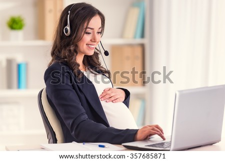 Call center. Young pregnant business woman with headset using a laptop in the office - stock photo