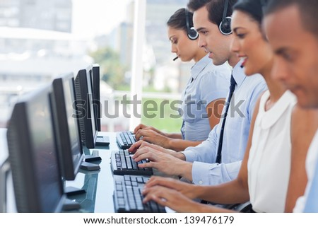 Call centre employees working on computers with their headset - stock photo