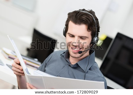Call centre operator or client services businessman wearing a headset looking up information in a file in order to be of assistance to the client - stock photo