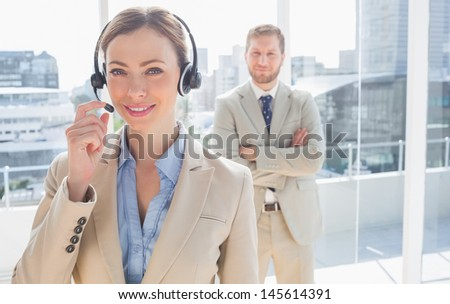 Call centre worker standing with colleague behind her in a bright office - stock photo