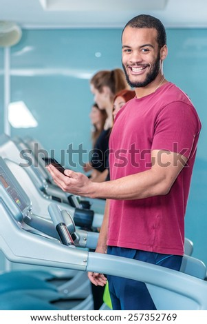 Call customer during sports activities. Sport runs on a treadmill and looking at the camera. Athlete dressed in sports uniforms and running in the gym. - stock photo