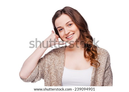 Call me! Beautiful young smiling woman looking at camera and gesturing mobile phone near ear while standing isolated on white - stock photo