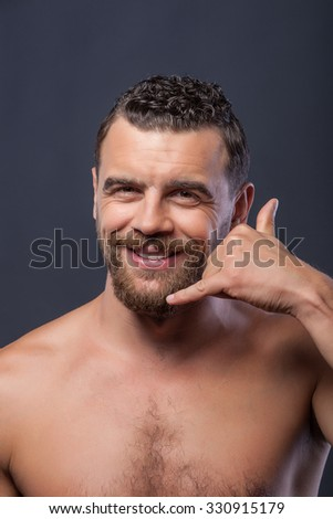 Call me. Cheerful young naked man is standing and making gesture of phone. He is raising arm to his ear and smiling. Isolated on grey background - stock photo