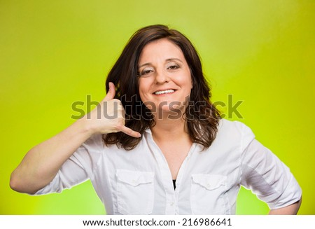 Call me gesture. Portrait middle aged single woman excited happy worker making showing dial my number sign with hand shaped like phone isolated green background. Positive human emotion face expression - stock photo