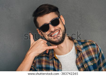 Call me! Portrait of cheerful young man gesturing telephone with his hand and looking at camera with smile while standing against grey background - stock photo