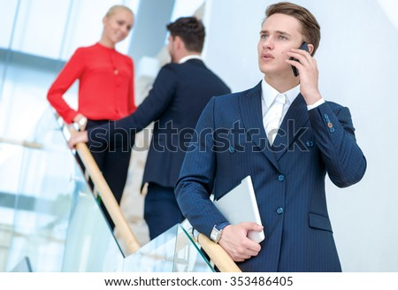 Call the customer. Confident young man talking on a cell phone and looking away while his colleagues talking in the background. - stock photo