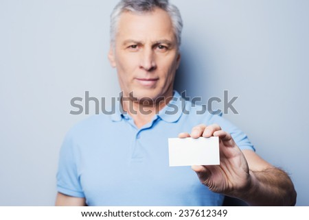 Call this number! Handsome senior man stretching out a business card and smiling while standing against grey background - stock photo