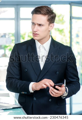 Call Waiting. Confident and successful businessman standing in an office and holding a mobile phone in his hand looking away - stock photo