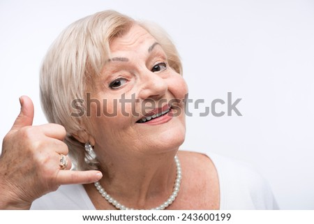 Call your grandparents. Closeup portrait of happy elderly woman with her hands imitating a phone call while standing against white background - stock photo