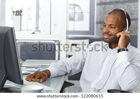Callcenter agent sitting at office desk, working on phone with headset.