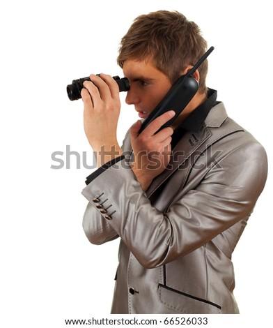 calling attractive young  spy man looking through binoculars - stock photo