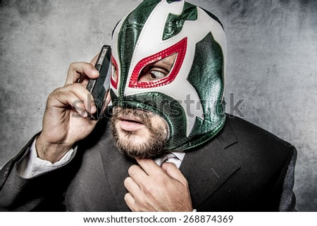 Calling, businessman angry with Mexican wrestler mask - stock photo