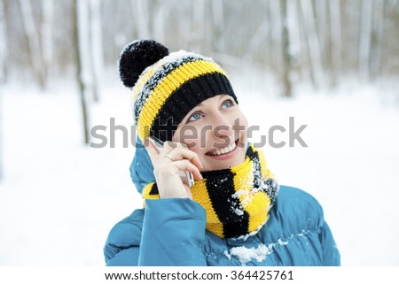 Calling by phone women. Portrait of a beautiful young woman in a turquoise feather bed and a knitted cap on a background of a winter park - stock photo