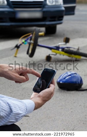 Calling emergency service after accident on the street - stock photo