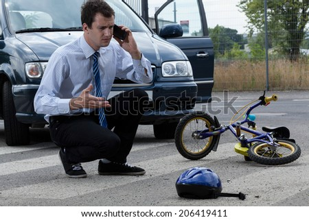 Calling for help after hitting little biker - stock photo