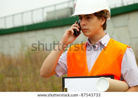 calling male architect with blueprint in construction site - stock photo