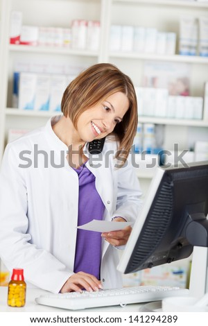 Calling pharmacist chemist while browsing on computer in the drugstore - stock photo