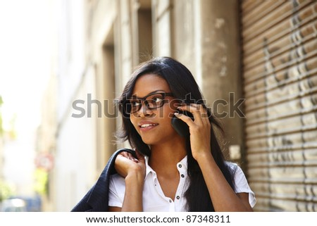 calling somebody by mobile telephone, walking on the street - stock photo