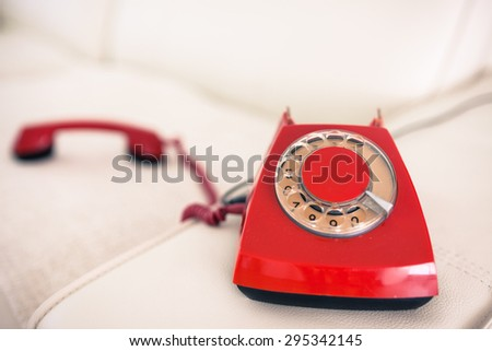Calling with a red retro phone on the sofa - stock photo