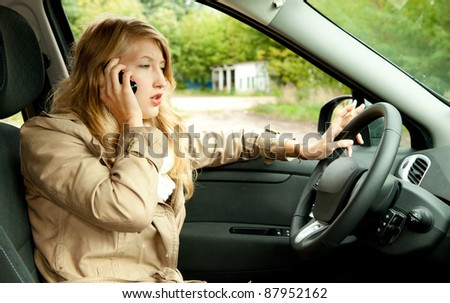 calling young beautiful woman driving her new car - stock photo